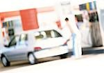Person filling up car at gas station, blurred Stock Photo - Premium Royalty-Free, Artist: Studio K, Code: 696-03399634