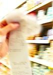 Hand holding receipt, supermarket shelves in background, blurred Stock Photo - Premium Royalty-Freenull, Code: 696-03399943