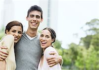 Young man standing with arms around two young women in urban park Stock Photo - Premium Royalty-Freenull, Code: 696-03400185