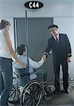 Man in wheelchair shaking hands with pilot in airport Stock Photo - Premium Royalty-Freenull, Code: 696-03400687