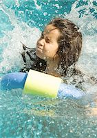 Girl in pool after jumping in, water splashing and eyes shut Stock Photo - Premium Royalty-Freenull, Code: 696-03401012