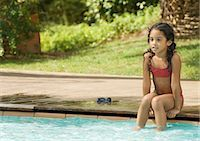 Girl sitting on edge of swimming pool with feet in water Stock Photo - Premium Royalty-Freenull, Code: 696-03401014