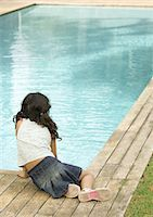 Little girl sitting by edge of swimming pool, rear view Stock Photo - Premium Royalty-Freenull, Code: 696-03401017