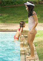 Girl standing by edge of swimming pool, second girl getting out in background Stock Photo - Premium Royalty-Freenull, Code: 696-03401025