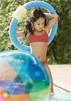 Girl in swimming pool, holding ring over head Stock Photo - Premium Royalty-Freenull, Code: 696-03401027