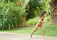Girl in bathing suit running in back yard Stock Photo - Premium Royalty-Freenull, Code: 696-03401028