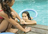 Girl helping second girl out of pool Stock Photo - Premium Royalty-Freenull, Code: 696-03401031