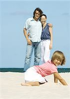 Girl digging in sand while parents stand in background Stock Photo - Premium Royalty-Freenull, Code: 696-03401197