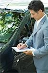 Insurance adjuster inspecting car Stock Photo - Premium Royalty-Freenull, Code: 696-03401684