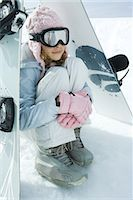 Preteen girl sitting on snow underneath propped up snowboards Stock Photo - Premium Royalty-Freenull, Code: 696-03401790