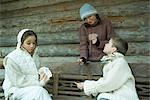 Young friends playing cards outdoors, dressed in winter clothing Stock Photo - Premium Royalty-Freenull, Code: 696-03401805