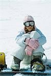 Young female snowboarder sitting on ground, hugging knees Stock Photo - Premium Royalty-Freenull, Code: 696-03401841