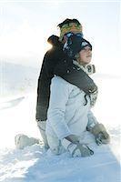 Mature man embracing teenage girl, both kneeling in snow Stock Photo - Premium Royalty-Freenull, Code: 696-03401923
