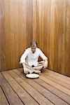 Man sitting with legs crossed on wooden floor, looking down at miniature rock garden, full length Stock Photo - Premium Royalty-Free, Artist: JTB Photo, Code: 696-03402030