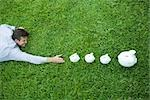 Man lying on grass, reaching for line of piggy banks Stock Photo - Premium Royalty-Free, Artist: ableimages, Code: 696-03402149