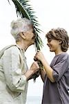 Grandmother and grandson face to face, holding palm leaf together, side view Stock Photo - Premium Royalty-Free, Artist: Arian Camilleri, Code: 696-03402323