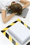 Woman sitting with her head down near a stack of paper surrounded by black and yellow tape Stock Photo - Premium Royalty-Free, Artist: Photocuisine, Code: 696-03402665