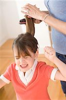 Girl Unhappy with having Hair Brushed Stock Photo - Premium Royalty-Freenull, Code: 600-03403633