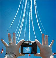 Women's Hands Holding Digital Camera, Taking Picture of Snowbirds at Air Show, CNE, Toronto, Ontario, Canada Stock Photo - Premium Rights-Managednull, Code: 700-03403781