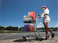 Low angle view of woman pushing trolley full of shopping bags, KwaZulu Natal Province, South Africa Stock Photo - Premium Royalty-Freenull, Code: 682-03404979