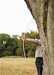 Young boy partially hidden by a tree aiming with a bow and arrow Stock Photo - Premium Rights-Managed, Artist: ableimages, Code: 822-03406700