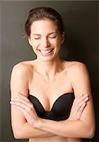 Smiling young woman wearing a strapless black bra Stock Photo - Premium Rights-Managednull, Code: 822-03406706