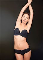 Young woman with arms crossed over head wearing black underwear Stock Photo - Premium Rights-Managednull, Code: 822-03406781