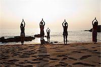 Women practicing yoga on beach at sunset Stock Photo - Premium Royalty-Freenull, Code: 614-03420405