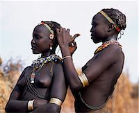 A Dassanech girl braids her sister's hair at her village in the Omo Delta. Much the largest of the tribes in the Omo Valley numbering around 50,000,the Dassanech (also known as the Galeb,Changila or Merille) and Nilotic pastoralists and agriculturalists. Stock Photo - Premium Rights-Managednull, Code: 862-03437084