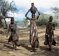Turkana girls return home from a Waterhole with water containers made of wood. Their cloaks are goatskin embellished with glass beads. Stock Photo - Premium Rights-Managednull, Code: 862-03437159