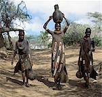 Turkana girls return home from a Waterhole with water containers made of wood. Their cloaks are goatskin embellished with glass beads. Stock Photo - Premium Rights-Managed, Artist: AWL Images, Code: 862-03437159