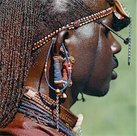Detail of a Maasai warrior's ear ornaments and other beaded or metal adornments. The Maasai practice of piercing ears in adolescence and gradually elongating the lobes is gradually dying out. This warrior's body and his long braids have been smeared with red ochre mixed with animal fat. Stock Photo - Premium Rights-Managednull, Code: 862-03437160