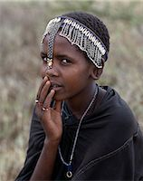 A young Maasai girl wears a headband decorated with chains and cowrie shells that signifies her recent circumcision. Clitodectomy was commonly practiced by the Maasai but it is now gradually dying out. Stock Photo - Premium Rights-Managednull, Code: 862-03437161