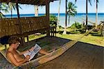 Philippines,Southern Leyte. Coral Cay Conservation volunteer relaxing in a hammock and studying dive plan charts. . Stock Photo - Premium Rights-Managed, Artist: AWL Images, Code: 862-03437311