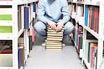 Young man crouches with pile of books in library Stock Photo - Premium Royalty-Free, Artist: Blend Images, Code: 693-03440817