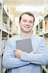 Portrait of man holding a book Stock Photo - Premium Royalty-Free, Artist: Matthias Tunger, Code: 693-03440840
