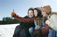 Three girls take self portrait with camera phone Stock Photo - Premium Royalty-Freenull, Code: 693-03440927