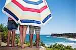 Friends under beach umbrella on patio overlooking ocean Stock Photo - Premium Royalty-Freenull, Code: 635-03441040