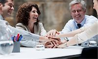 Business people stacking hands in meeting Stock Photo - Premium Royalty-Freenull, Code: 635-03441166