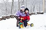 Boy and Girl Playing with Tricycle in Snow Stock Photo - Premium Rights-Managed, Artist: Michael Filonow, Code: 700-03451465