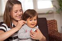 Teenage Girl with Baby Boy Listening to MP3 Player, Mannheim, Baden-Wurttemberg, Germany Stock Photo - Premium Royalty-Freenull, Code: 600-03456197