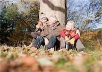 Grandparents leaning against tree with grandson Stock Photo - Premium Royalty-Freenull, Code: 635-03457417