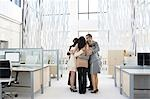 Business people huddling in modern office Stock Photo - Premium Royalty-Free, Artist: Kevin Dodge, Code: 635-03457843