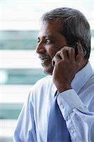Head shot of mature Indian business man talking on phone Stock Photo - Premium Royalty-Freenull, Code: 655-03457911
