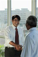 Indian man shaking hands and smiling Stock Photo - Premium Royalty-Freenull, Code: 655-03458060