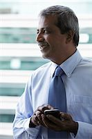 Profile of Indian man texting on phone Stock Photo - Premium Royalty-Freenull, Code: 655-03458076