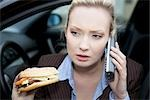 Businesswoman holding a hamburger and phoning, close-up Stock Photo - Premium Rights-Managed, Artist: F1Online, Code: 853-03459150