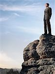 Businessman Standing on top of Cliff