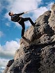 Businessman Climbing up Cliff