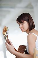 Woman sitting with accoustic guitar Stock Photo - Premium Royalty-Freenull, Code: 693-03474207